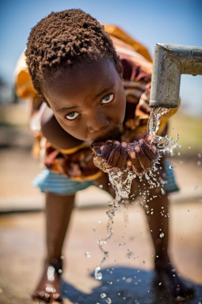 Malawi child drinks water from a water pump